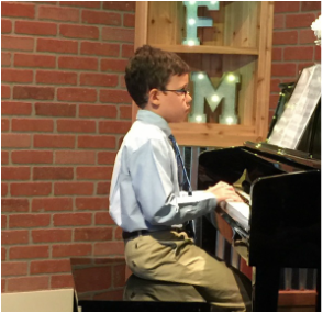 Young Boy playing the Piano in recital